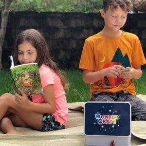 Girl and boy reading and plyaing outside with books and toys from Wonder Crate Kids Subscription Box For Kids
